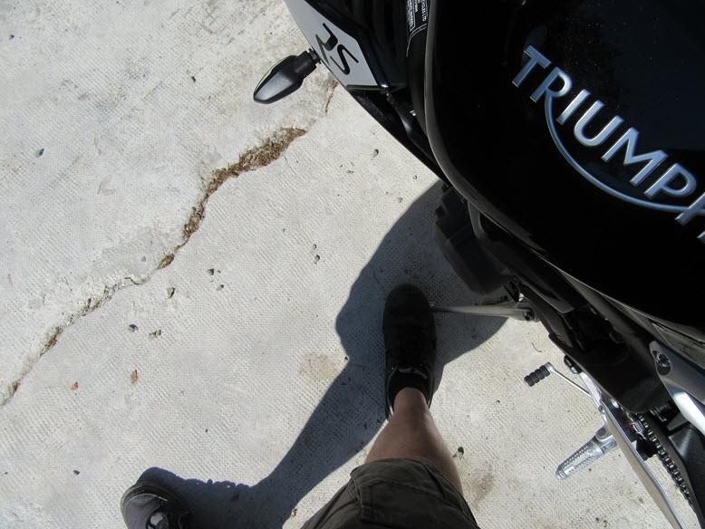 Avec mon pied je viens verrouiller la béquille de la moto
